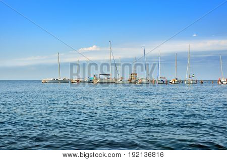 Yachts And Sailing Boats Are On The Dock. The Small Naval Vessels Are In The Harbor On A Background