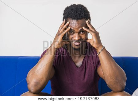 Handsome worried, bothered, sad, muscular black man sitting on couch at home, looking at camera