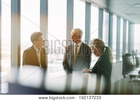Three business colleagues standing behind the glass and discussing work. Corporate professional having a standing meeting in modern office.