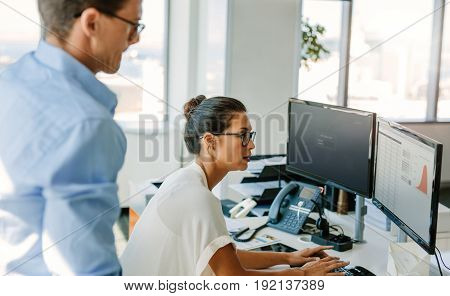 Mature businesswoman working on computer with male colleague standing by. Business man and woman at work desk looking at computer monitor.