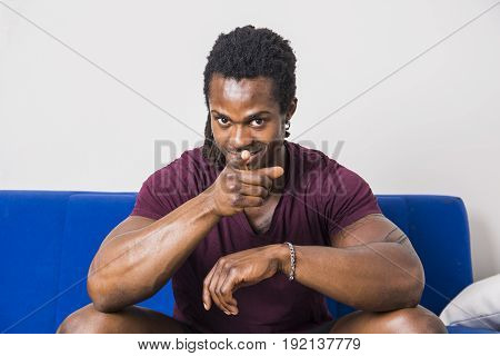 Handsome muscular black man sitting on couch at home, looking confident and pointing finger to camera with a smile on his face