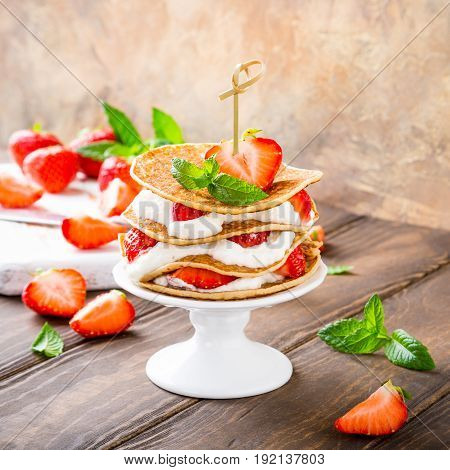 Small cake made of pancakes with cream and strawberries on white porcelain cake stand. Children's party background. Healthy food concept, copy space.