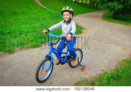 A happy child rides bicycle in  green city park outdoors on a footpath. Children's games to spend time with children in the open air