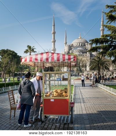 Istanbul Turkey - April 16, 2017: Tourist buying fast food meal from a traditional Turkish Simit (Bagel) cart in Sultan Ahmed Square with Sultan Ahmed Mosque in the background