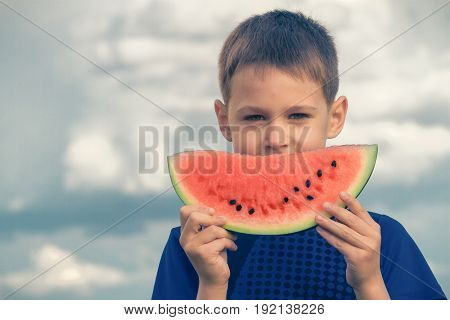 Child with watermelon against blue sky. Healthy food concept