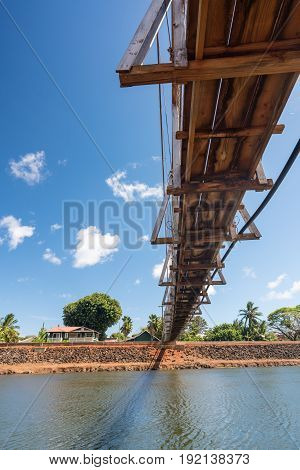 View from underneath the famous wooden suspension swinging bridge to cross the river in Hanapepe Kauai