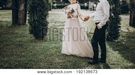 Stylish Wedding Bride And Groom Walking In Sunny Park Holding Hands. Modern Happy  Couple Holding Fa
