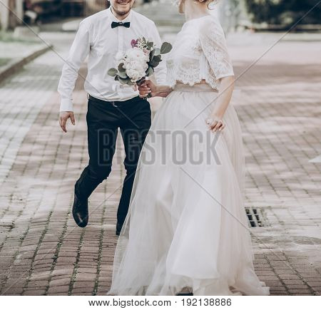 Stylish Wedding Bride And Groom Having Fun In Sunny Park, Happy Moment. Modern Couple Running And Sm