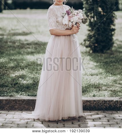Stylish Wedding Bride With Bouquet. Modern Bride Posing And Smiling, Lips And Earrings Close Up. Fin