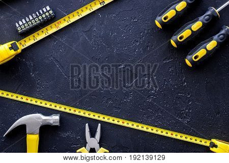 Tools for repairing on black stone table background top view copyspace.
