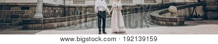 Stylish Wedding Couple With Bouquet. Modern Bride And Groom Holding Fashionable Bouquet  And Posing