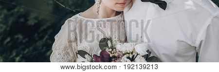Stylish Wedding Couple With Bouquet. Modern Bride And Groom Holding Fashionable Bouquet And Embracin