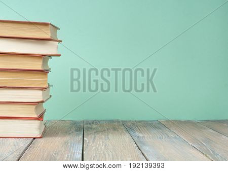 Colorful books on the table against the background of green wall. Education concept. Copy space for text