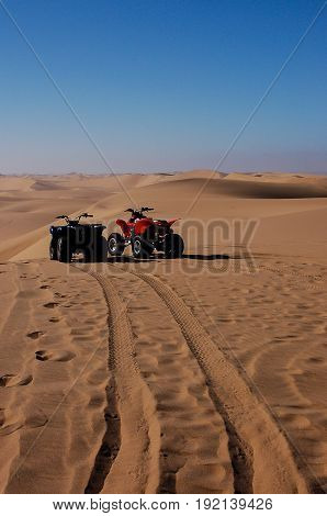 Red and Blue Dune Buggies waiting for their riders; revving for the next race across the dunes of the Kalahari Desert.