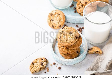 Stack of chocolate chip cookies on blue stone plate with glass of milk on light gray background. Selective focus. Copy space.