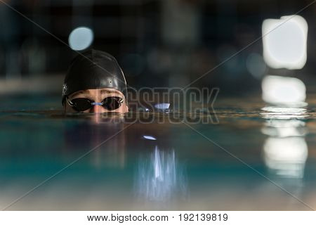 Close up of the top half of a male swimmers head submerged in a swimming pool