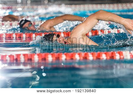 Side view of three male swimmers doing free style in different swimming lanes