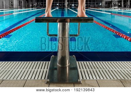 Man's feet standing on the starting blocks infront of swimming lane at a pool