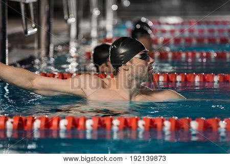 Close up of a male swimmer holding the edge of a swimming pool