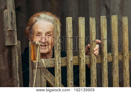 Portrait of an elderly woman in the village near the wooden fence.