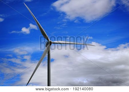 Windmills wind power producing electicity with blue sky and clouds