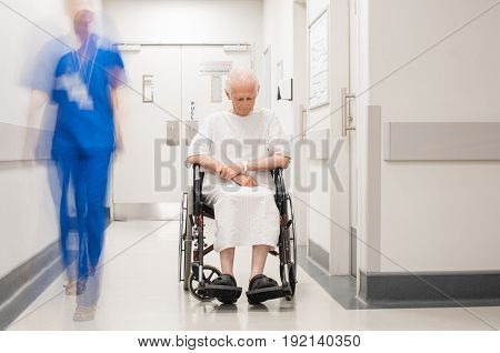Sad old man sitting on wheelchair in hospital corridor. Depressed senior patient in hospital hallway while nurse passing by. Blur motion of nurse passing beside a elderly patient with alzheimer.