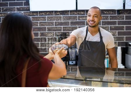 Young waiter giving parcel to customer at counter in cafeteria. Young waiter at cafe giving take away salad to woman customer. Happy african man selling food to woman.