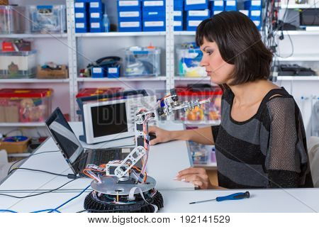 Female in robotics laboratory. Young woman experiment with robot