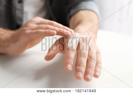 Man applying cocoa butter lotion onto hand over table