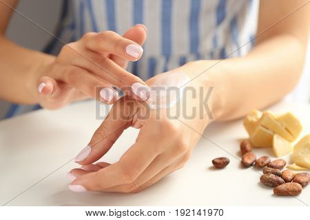 Woman applying cocoa butter lotion onto hand over table