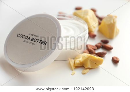 Jar with cocoa butter lotion on white background
