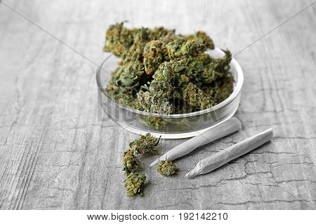 Heap of weed buds and Petri dish with cigarettes on grey background