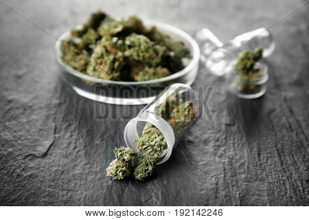 Heap of weed buds in glassware on grey background