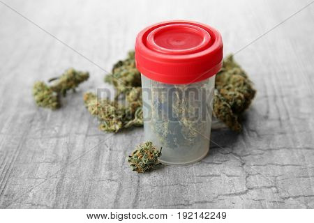 Weed buds and plastic container on grey background