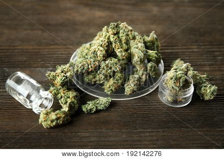 Heap of weed buds and glassware on wooden background