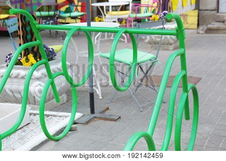 Empty colorful bicycle rack near cafe