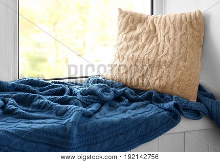 Pillow and warm knitted plaid on a window sill
