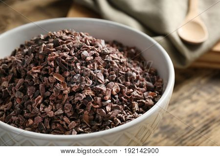 Cocoa nibs in bowl on wooden table