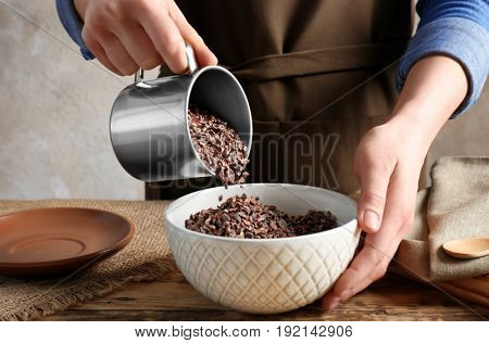 Person pouring cocoa nibs from cup into bowl on table