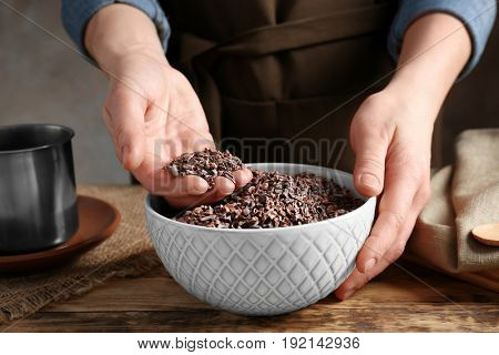 Person with cocoa nibs in hand over bowl on table