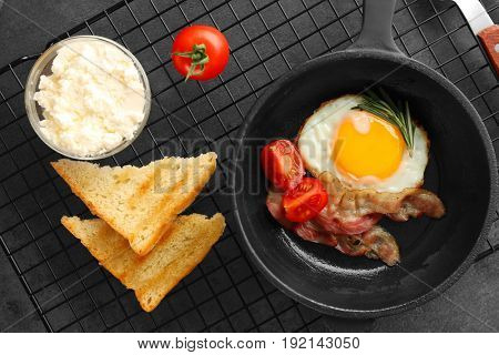Frying pan with tasty egg and bacon for breakfast on table