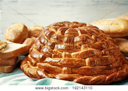 Baked round loaf and variety of bread on table