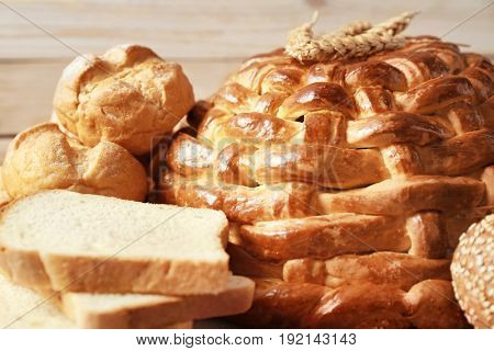 Baked round loaf and variety of bread, closeup