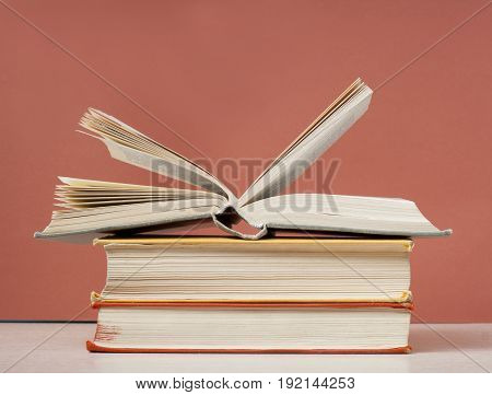 Open book, hardback books on the table on the background of red wall. Copy space for text Back to school. Education concept.
