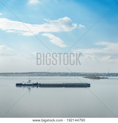 barges with boat on river and clouds in blue sky