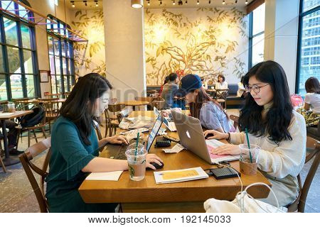 SEOUL, SOUTH KOREA - CIRCA JUNE, 2017: people at Starbucks in Seoul. Starbucks Corporation is an American coffee company and coffeehouse chain.