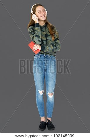 Teenage girl smiling and listening music by headphones