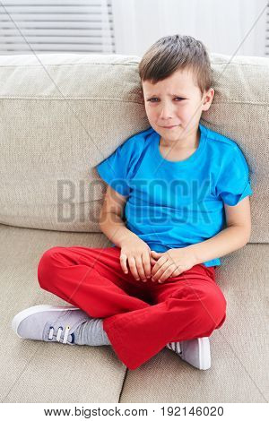 Top view of small boy crying on sofa. Dissapointed small child