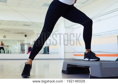 Cropped shot of skinny woman legs doing step aerobics in gym. Wearing black sneakers for gym