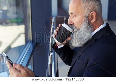 Close-up of serious old gentleman drinking coffee and surfing in phone while leaning on handrail